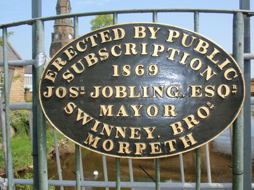 1869 brass plaque on a footbridge over the River Wansbeck, Northumberland.