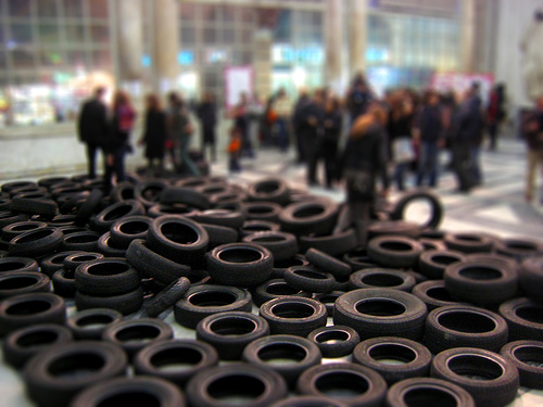 Dozens of tires lined up on the ground, with people in the background.