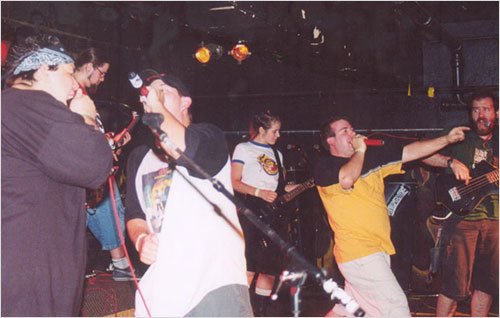 The band and friends rocking out on stage in 2003 and making music as a team.