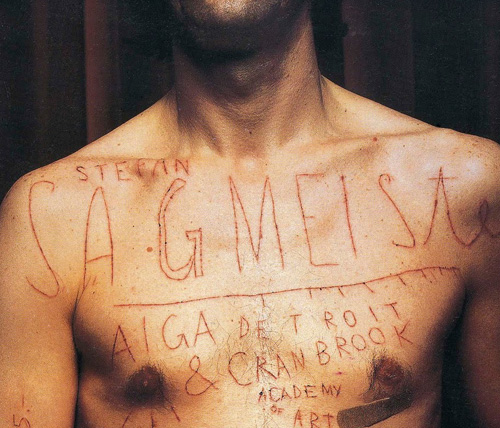 Stefan Sagmeister's naked torso with letters carved into it