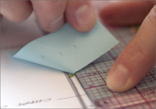 Ripping a sticky note with a ruler.